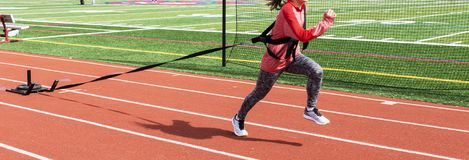 Female athlete pulling sled with weight down a red track. A high school female is pulling a weighted sled while sprinting down a red track during track and field royalty free stock images