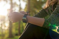 Female athlete putting on her her smart watch to monitor workout performance. Lifestyle wearable technology concept. Stock Photos