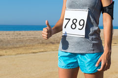 Female athlete with race start number doing thumbs up. Close up body part of female athlete with race start number doing thumbs up outdoors Royalty Free Stock Photos