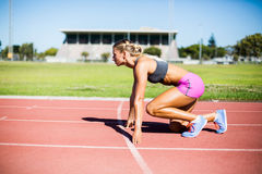 Female athlete ready to run on running track Stock Photo