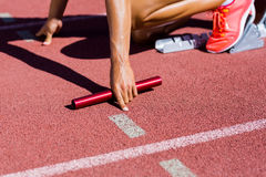 Female athlete ready to start the relay race. On the running track royalty free stock images