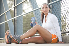 Female athlete resting. Attractive female athlete resting, holding a water bottle looking past camera Royalty Free Stock Images