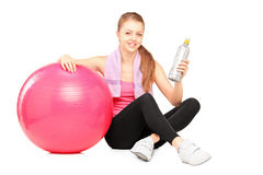 Female athlete resting next to a pilates ball Royalty Free Stock Photo