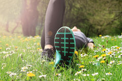 Female athlete resting after workout. Woman lying down on grass. Sport, Running, Jogging, Healthy lifestyle concept Royalty Free Stock Photo