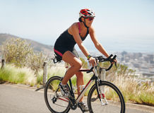 Female athlete riding cycle on country road Stock Images