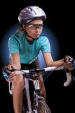 Female athlete riding her race bike isolated over black Royalty Free Stock Photos