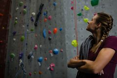 Athlete with rope looking up while standing by climbing wall in gym royalty free stock photography