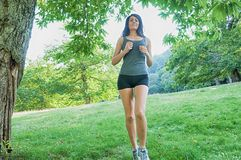 Female athlete/runner running on park: jog workout wFemale athlete/runner running on park - jog workout well-being. Female athlete and runner running on park Royalty Free Stock Images