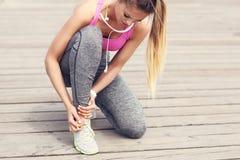 Female athlete runner touching foot in pain outdoors. Picture of female athlete runner touching foot in pain outdoors stock photo