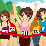 Female Athlete Runner Winning. Beautiful brunette female athlete runner woman winning marathon crossing finish line before other runners Royalty Free Stock Photography