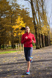 Female athlete running in autumn park Stock Images