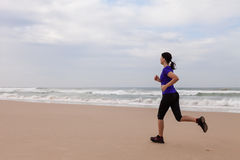 Female athlete running at the beach royalty free stock image