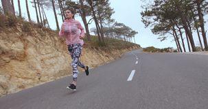 Female athlete running on country highway stock video footage