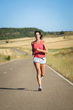 Female athlete running in country road. Female fit athlete on running workout in country road . Sporty powerful woman exercising on summer Stock Photo