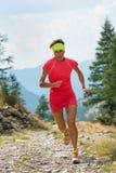 Female athlete running on mountain trail stock photo