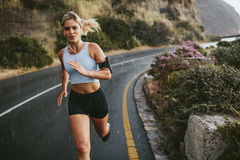 Female athlete running outdoors on highway Royalty Free Stock Photography
