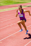 Female athlete running on the racing track Stock Photos