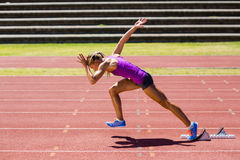 Female athlete running on the racing track Royalty Free Stock Image