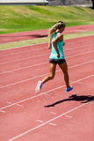 Female athlete running on the racing track Stock Images