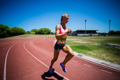Female athlete running on the racing track Royalty Free Stock Images