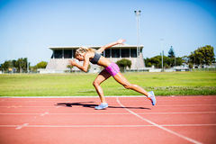 Female athlete running on the racing track Stock Image