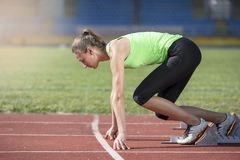 Female athlete running on the racing track on a sunny day.  Royalty Free Stock Photos