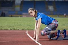 Female athlete running on the racing track on a sunny day.  Royalty Free Stock Photography