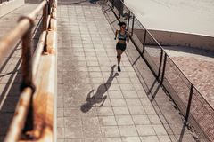 Female athlete running on seaside boardwalk Stock Photo