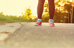 Female athlete in running shoes ready for a run on a forest path Royalty Free Stock Photo