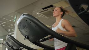 Female athlete is running on treadmill in gym. Young lady moves actively on aerobic machine, magnetic tape of mechanical treadmill rotates due to efforts of stock video footage