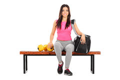 Female athlete sitting on a bench with her training equipment Royalty Free Stock Photos
