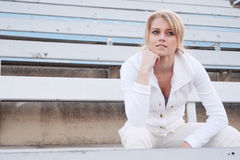Female athlete sitting in the bleachers Royalty Free Stock Image
