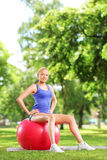 Female athlete sitting on a  pilates ball in park Stock Photography