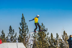 Female athlete snowboarder jump flight on blue sky background Royalty Free Stock Photos