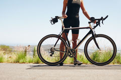 Female athlete standing with her bicycle Stock Photos