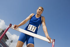 Female Athlete Standing At Hurdle Royalty Free Stock Images