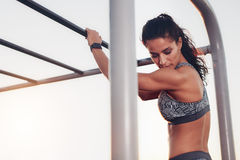 Female athlete standing by monkey bars. Portrait of strong young woman standing by monkey bar exercise equipment outdoors. Fitness woman in sportswear looking Royalty Free Stock Images