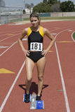 Female Athlete At Starting Block On Race Track Stock Photo
