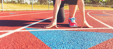 Female athlete on the starting line of a stadium track. Preparing for a run stock image