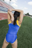 Female Athlete Stretching Arm On Field. Rear view young female athlete stretching on field Royalty Free Stock Image