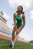 Female Athlete Stretching On Field Stock Images