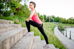 Female athlete stretching and running along a river at dusk Royalty Free Stock Photography