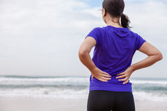 Female athlete suffering from a back injury Stock Photo
