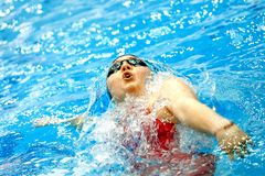 Female athlete swimming backstroke in pool. Chelyabinsk, Russia - March 13, 2018: female athlete swimming backstroke in pool during Championship Ural Federal Royalty Free Stock Images