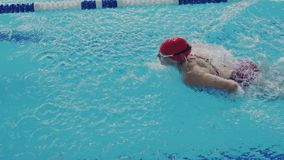 Female athlete swims with a butterfly style. A woman swimmer takes part in swimming competitions. She push off from the. Female athlete swims with a butterfly stock footage