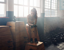 Female athlete taking break after exercising at gym Royalty Free Stock Photography
