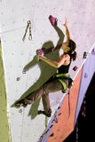 Female Athlete taking Hold on Climbing Wall at Night Royalty Free Stock Images