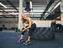 Female athlete taking rest after tough crossfit workout. Woman sitting on tire and smiling at camera at gym. Crossfit female athlete taking rest after working stock images