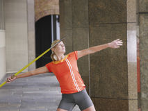 Female Athlete Throwing Javelin In Portico Stock Photo