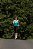 Female athlete training by running through trees Royalty Free Stock Photography